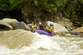 Whitewater river rafting group of mixed tourist men and women with guided by professional pilot on in ecuador Royalty Free Stock Photos