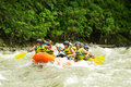 Whitewater river rafting group of mixed tourist men and women with guided by professional pilot on in ecuador Stock Photography