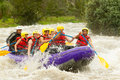Whitewater river rafting group of mixed tourist men and women with guided by professional pilot on in ecuador Royalty Free Stock Images