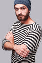 Who is the man confident young bearded in striped clothing keeping arms crossed and looking at camera while standing against grey Stock Images