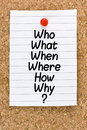 Who what when where why questions list of how on lined note page affixed on cork board with a red small thumb tac for gathering Royalty Free Stock Photography