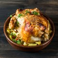 Whole baked chicken with mushrooms and potatoes in a baking dish on a table. Baked turkey. Christmas dish. Easter