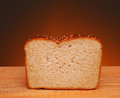 Whole graijn bread a slice of grain on a wood table and a war light to dark background Stock Image