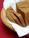 Whole grain bread loaf of with a few cut slices sitting in a towel lined basket on a red tablecloth Royalty Free Stock Photography