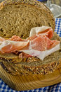 Whole grain bread and prosciutto ham thinly sliced Stock Photos