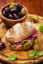 Whole grain sandwich with italian salami goat cheese and fresh olives Stock Photo