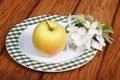 Whole green apple with flowers on a white plate table Royalty Free Stock Photography