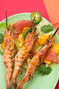 Whole grilled scampi with citrus salad close up of large shrimps on bamboo sticks served spicy avocado Royalty Free Stock Images