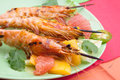 Whole grilled scampi with citrus salad close up of large shrimps on bamboo sticks served spicy avocado Stock Photography