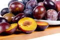 Whole and halved fresh red plums on a plate wooden counter ready to be used in a tasty dessert or eaten as a healthy snack Royalty Free Stock Photography