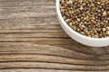 Whole hemp seeds in a small bowl on a grained wood Royalty Free Stock Photos