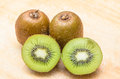 Whole kiwi fruit and his sliced segments on chopping block Royalty Free Stock Photography