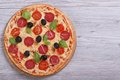 Whole pizza with salami tomato cheese olives and basil on the table top view Royalty Free Stock Photo