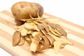Whole potato and peels lying on wooden cutting board heap of Royalty Free Stock Images