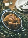 Whole roasted chicken decorated with olive tree branch on table Royalty Free Stock Photo