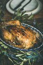Whole roasted chicken with garlic over wooden table background Royalty Free Stock Photo
