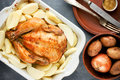 Whole roasted chicken with golden crust garnished potato