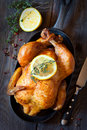 Whole roasted chicken with lemon and thyme on a pan rustic style Royalty Free Stock Images