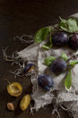 Whole and slice prunes with leafs on rustic background jute napkin Royalty Free Stock Photos