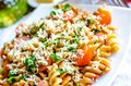 Whole wheat fusilli pasta with cheese and cherry tomatoes Royalty Free Stock Photo