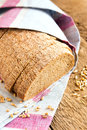 Wholegrain bread with wheat grains on linen napkin and rustic wooden background table Royalty Free Stock Images