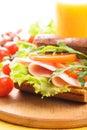 Wholegrain sandwich with ham tomato lattuce and arugula with glass of orange juice breakfast Royalty Free Stock Image