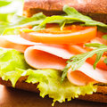 Wholegrain sandwich with ham tomato lattuce and arugula with glass of orange juice breakfast Stock Photos