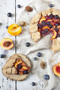 Wholemeal french galette with fruits sliced apricots peaches and blueberries on vintage rustic background with fresh fruits Royalty Free Stock Images