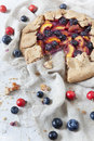 Wholemeal french galette with fruits sliced apricots peaches and blueberries on vintage rustic background with fresh fruits and ro Royalty Free Stock Images
