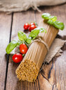 Wholemeal spaghetti close up shot on an old wooden table Royalty Free Stock Images