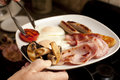 Wholesome cooked english breakfast with fried eggs sausages tomato mushrooms bacon and hash browns Stock Image