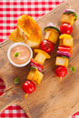Wholesome country halloumi and vegetable kebabs served on a wooden board on a picnic table covered with a fresh red white Royalty Free Stock Image