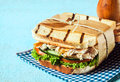 Wholesome country toasted sandwich in a wrapper with shredded chicken frilly lettuce cucumber and tomato served on a blue and Stock Image
