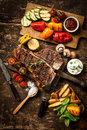 Wholesome spread with t bone steak and veggies or porterhouse served an assortment of healthy roasted vegetables savory dips on a Royalty Free Stock Image