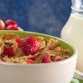 Wholewheat cereal with fresh strawberries in bowl and milk in the back selective focus focus on the strawberry Royalty Free Stock Photography