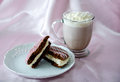 Whoopee pie and hot chocolate a delicious cup of with whipped cream a cake with white cream filling pink white Royalty Free Stock Image