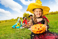 Wicked girl in witch dress with halloween pumpkin costume holds and smiles her friends on background Royalty Free Stock Image