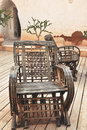 Wicker armchair with old wall background on patio Royalty Free Stock Photo