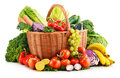 Wicker basket with assorted organic vegetables and fruits on white Royalty Free Stock Photo