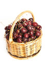 Wicker basket full of cherry berries on white background Stock Photo