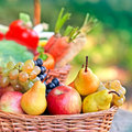 Wicker basket with organic fruits is full of Stock Images