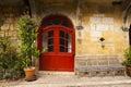 Wicker bench red door Saint-Cyprien Dordogne Royalty Free Stock Photo
