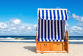 Wicker chair on sandy Kolobrzeg beach, Baltic Sea, Poland Royalty Free Stock Photo