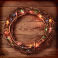 Wicker christmas wreath high angle view of a with holiday lights on a rustic wooden surface square format with an instagram look Stock Photography