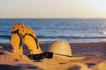 Wicker hat sandaland glasses on the sandy beach Royalty Free Stock Photos