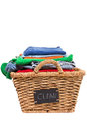 Wicker laundry basket filled with clean clothes stack of folded colorful ready for ironing a handwritten label on the side of Stock Photos