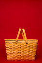 Wicker picnic basket on a red background brown with copy space Royalty Free Stock Image