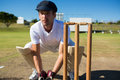 Wicket keeper crouching by stumps during match Royalty Free Stock Photo