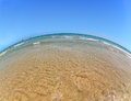 Wide angle sandy beach on the Mediterranean Sea, blue sky and sea, the fish-eye. Royalty Free Stock Photo