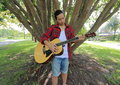 stock image of  Wide angle shot of portrait of handsome young man playing acoustic guitar in the park outdoors with a large tree background.